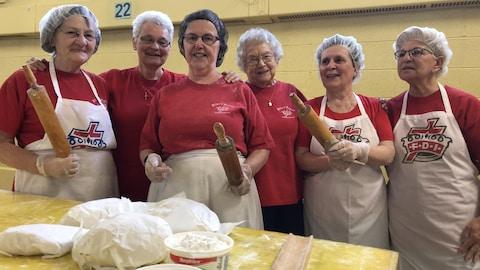 Six femmes avec leurs rouleaux à pâtes et leurs tabliers devant une table avec de la pâte.