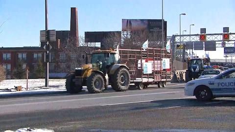 Un convoi de tracteurs traverse le pont Jacques-Cartier