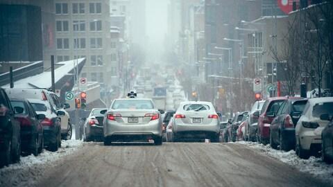 Des voitures roulent en hiver dans le Quartier des spectacles, à Montréal.