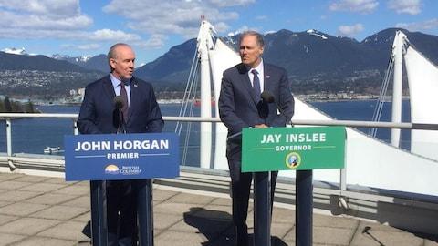 Deux hommes sont devant des podiums avec micro sur une place extérieure avec un paysage de montagnes à l'arrière-plan.