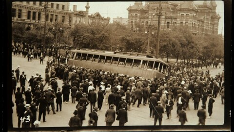 Une photo en noir et blanc d'une foule devant un tramway.