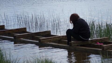 Une adolescente est assise seule sur un quai