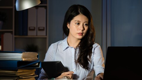 Une femme travail à son bureau la nuit.