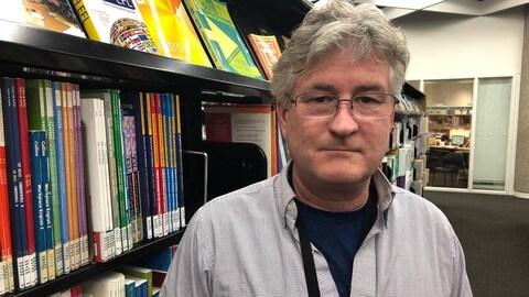 Un homme à lunettes devant une étagère de livres.