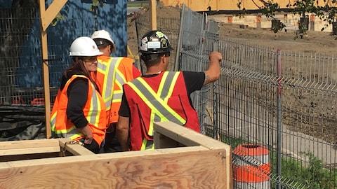 Trois travailleurs de la construction avec des vestes orange à l'entrée du site de construction.