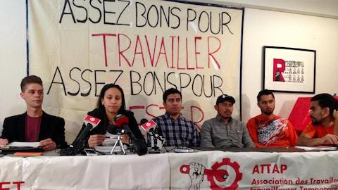 Cinq hommes et une femme en conférence de presse devant une affiche « Assez bons pour travailler, assez bons pour [illisible] »