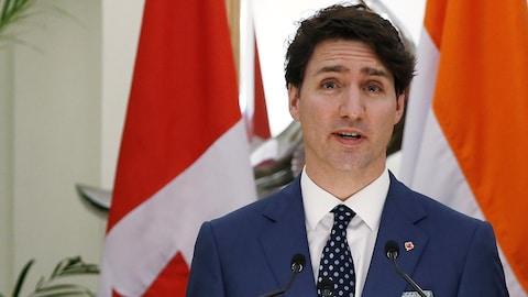 Justin Trudeau debout à une tribune fait une déclaration.