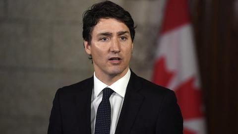 Le premier ministre Justin Trudeau devant un drapeau du Canada.