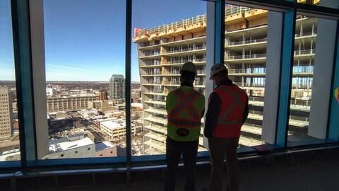 Deux personnes en casques et en veste réfléchissantes regardent la structure d'une tour en construction du haut d'une autre tour, surplombant le quadrillage des rues de Winnipeg.