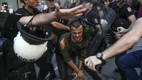 Un manifestant turc est repoussé par des policiers munis de boucliers lors de la manifestation LGBT à Istanbul.