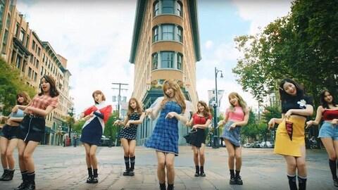Neuf jeunes femmes dansent dans une rue devant un hôtel de Vancouver.