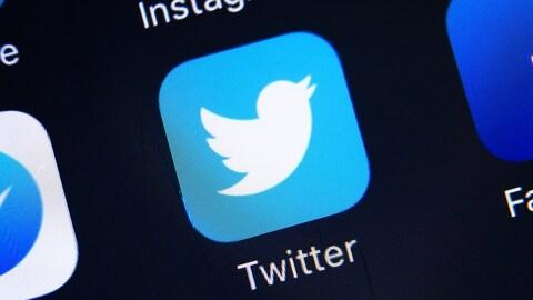 Une photo d'un écran de téléphone montrant différentes icônes d'applications, dont celle de Twitter, au centre.