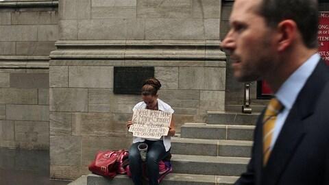 Un homme en complet passe devant une femme tenant un panneau pour demander de l'argent dans la rue