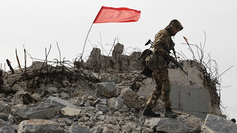 Un soldat monte la garde sur les ruines d'un bâtiment où flotte un drapeau.