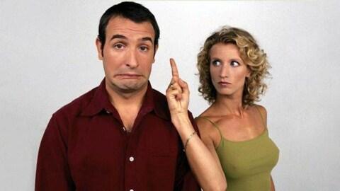 Jean Dujardin grimace et Alexandra Lamy le menace en pointant son doigt près de son visage dans la série  Un gars une fille .