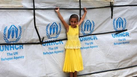 Une jeune Syrienne devant une tente du Haut-Commissariat des Nations unies pour les réfugiés au Liban