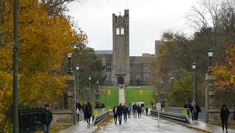 Un campus d'université avec des étudiants qui marchent, c'est l'automne