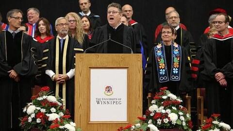 Un homme donne un discours derrière un pupitre de conférence
