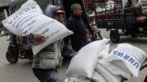 Un homme transporte un sac au logo de l'UNRWA sur son épaule.