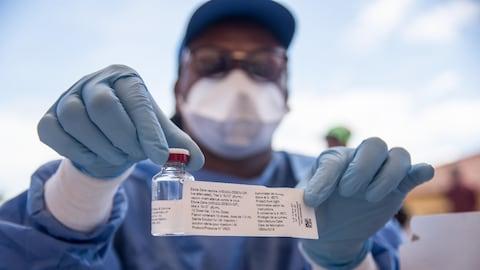 Un homme portant un masque, des gants de plastique, un tablier et des lunettes montre une petite fiole et son étiquette.