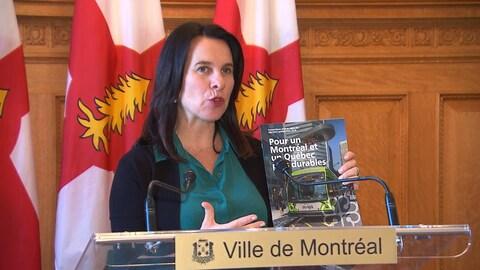Une femme tenant un livret sur lequel on peut lire « Pour un Montréal et un Québec plus durables » parle derrière un lutrin. Cette femme se trouve devant des drapeaux.