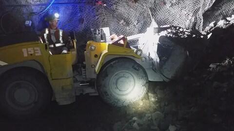 Une pelleteuse dans une mine soulève une pile de roches cassées sous terre.