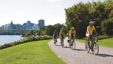 Des cycliste sur une piste cyclable en bordure de la rivière des Outaouais. Ottawa en arrière-plan.