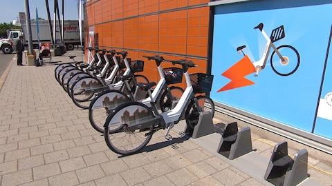 Une rangée de vélos fixés à leur borne.