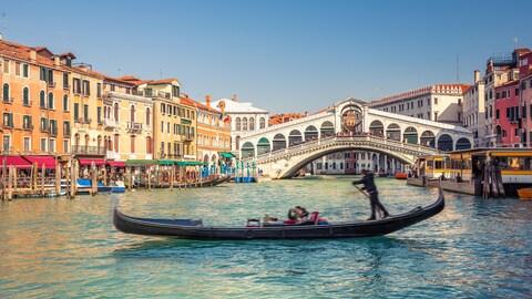 Une photo montrant le pont du Rialto à Venise. En avant-plan, une gondole traverse le canal.