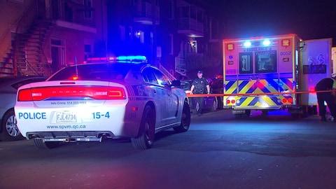 Une voiture de police est stationnée dans une rue résidentielle avec ses gyrophares allumés derrière un cordon de sécurité et une ambulance qui a aussi ses gyrophares allumés dans la nuit.