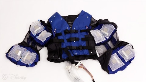 Une photo de la veste haptique bleue et noire déposée sur une surface blanche. Les manches de la veste sont ouvertes, ce qui permet de voir les sacs gonflables carrés.
