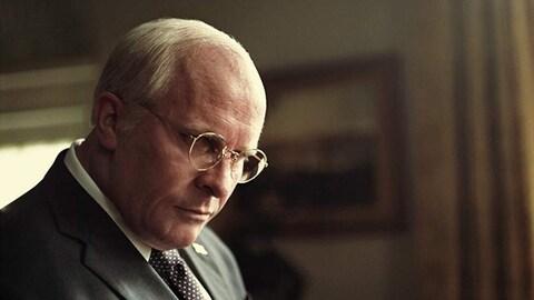 Christian Bale, dans le rôle de Dick Cheney, a la tête penchée et regarde vers le bas.