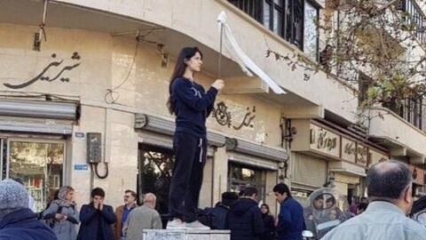 Une Iranienne, tête nue, brandit un bâton au bout duquel flotte son voile.