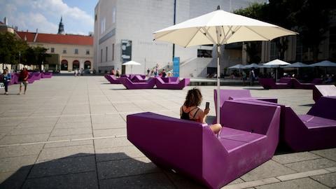 Une femme est assise à l'ombre au centre du MuseumsQuartier de Vienne, en Autriche.