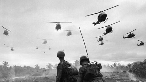 Des hélicoptères de guerre survolant le territoire vietnamien. Deux soldats regardent le spectacle à partir du sol.