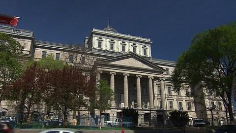 Le bâtiment en pierres grises se compose de six grandes colonnes à l'entrée. L'entrée est barrée par des grilles.