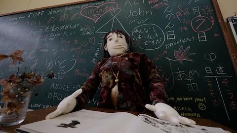 Une poupée grandeur nature d'une enseignante devant le tableau d'une salle de classe.