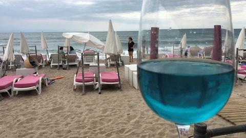 Un verre de vin est posé sur une table. Quelques vacanciers sont assis sur des chaises longues au bord de la plage.