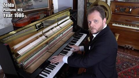 Vinheteiro, habillé en smoking, joue du piano en regardant la caméra.
