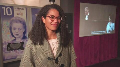 Angela Cassie sourit devant un panneau avec l'agrandissement du billet, où l'on voit l'image de Viola Desmond qui sourit elle aussi.