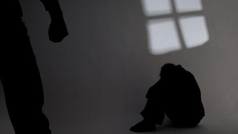 Une personne est assise par terre et une autre personne au premier plan a le poing serré.