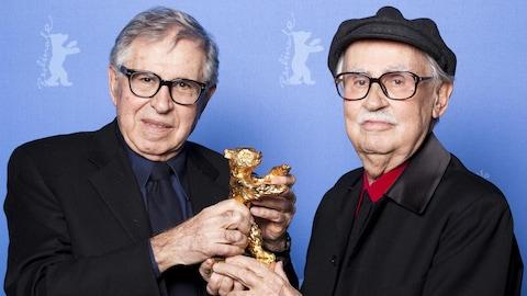 Les réalisateurs Paolo et Vittorio Taviani posent ensemble devant un fond bleu.