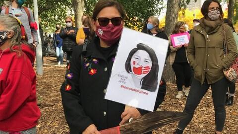Une femme innue masquée porte une pancarte de Joyce Echaquan.