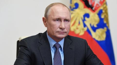 Vladimir Poutine est assis et regarde devant lui, avec un drapeau russe en arrière-plan.