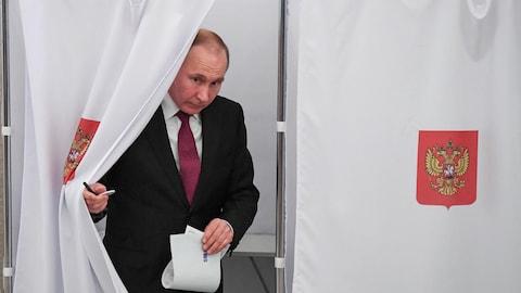 Vladimir Poutine sort d'un bureau de vote.