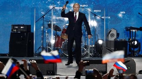 Le président Vladimir Poutine se tient debout sur une scène, micro levé dans la main dans une foule l'acclamant.