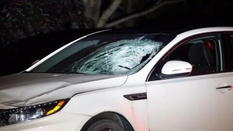 On voit une voiture blanche endommagée après une collision, son pare-brise pratiquement réduit en miettes du côté du conducteur.