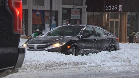 Une voiture dans la neige au bord d'une rue.