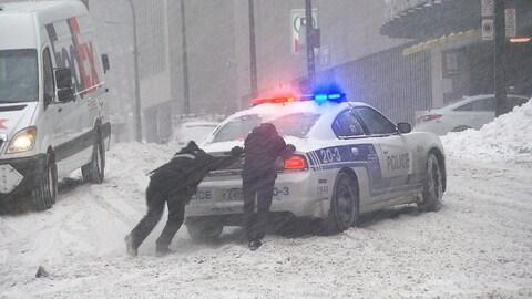Deux personnes poussent une voiture de police sur la chaussée enneigée.