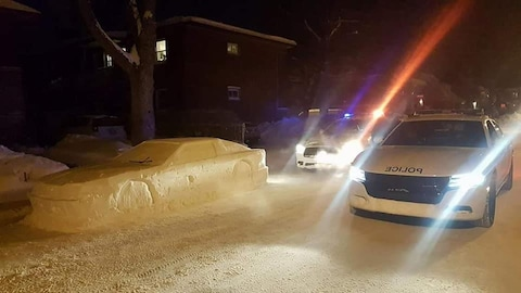 Deux voitures de police encadrent une voiture sculptée dans la neige.